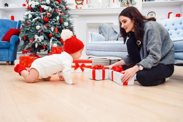 床の上に座っている彼のお母さんの近くのクリスマスプレゼントに寄せ木細工の上でクロール愛らしい愛らしい幼児。
