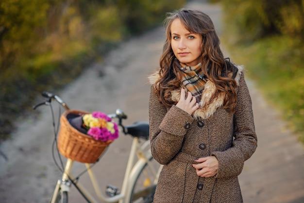 バスケットにピンクと黄色の花を持つ女性の自転車の近くに立っている秋のコートで美しい少女。