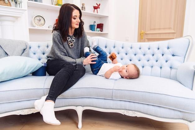 かわいい幼児は青いソファに横たわって、幸せな若いママが彼の足をこねて幸せにします。