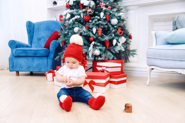 幼児男の子はクリスマスギフトボックスで遊んでお祝い服を着ています。クリスマスと新年の休日の概念。