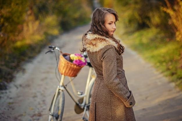 秋の木々の背後にあるバスケットにピンクと黄色の花を持つ女性の自転車の近くに立っている秋のコートで美しい少女。