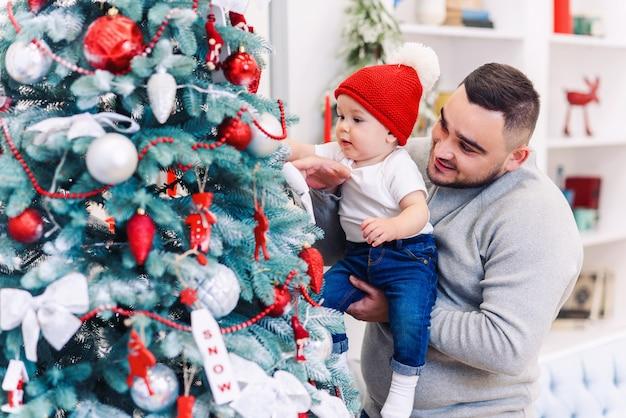 男とかわいい赤ちゃんは、新年を祝う準備ができています。幸せな父は、クリスマスの夜にクリスマスツリーの近くで彼の幼い息子と遊ぶ。