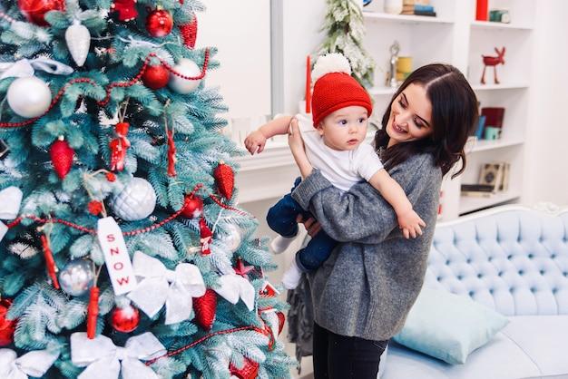 クリスマスの夜にクリスマスツリーの近くの彼女の幼い息子と楽しんで幸せな美しい母。