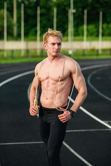 スタジアムで縄跳びと筋肉スポーツの若い男。身体トレーニング、トレーニング。