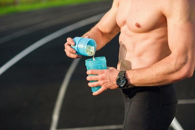スタジアムでシェーカーでスポーツ栄養を準備する筋肉の若い男。瓶の中のタンパク質