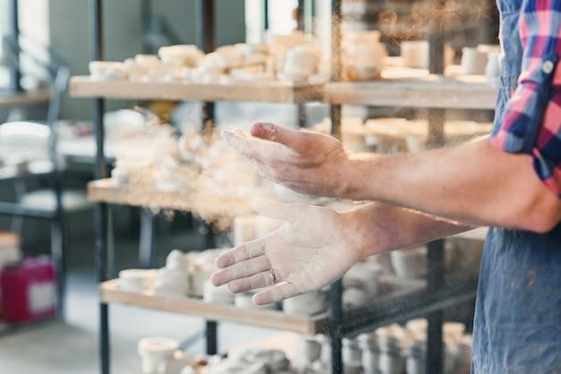 中年男性の手が粉で手をたたきます。