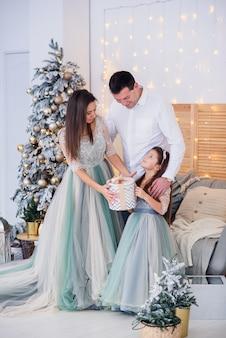 Счастливая девушка распаковывает подарочные коробки с родителями, стоя возле елки. счастливая прекрасная семья.
