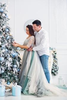 愛のカップルはクリスマスツリーの近くに一緒に立ち、お互いを見てください。