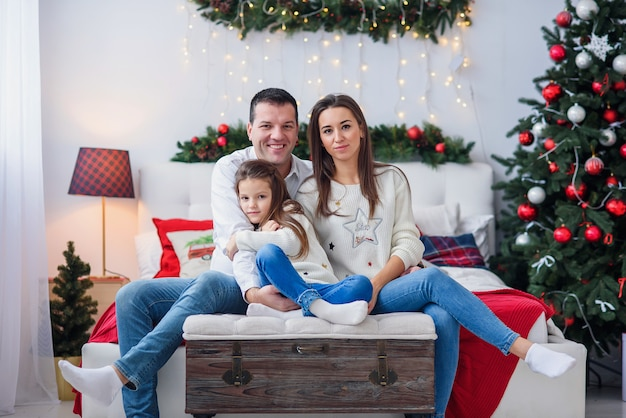 クリスマスツリーの近くに座っている小さな子供を持つ親