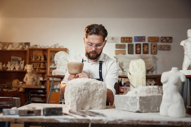 Резчик по камню работает с деревянным молотком и долотом на известняке.