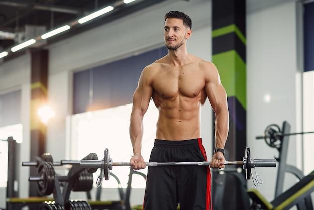 モダンなジムでバーベルで上腕二頭筋運動をしている魅力的な男。スポーティで健康的なコンセプト。