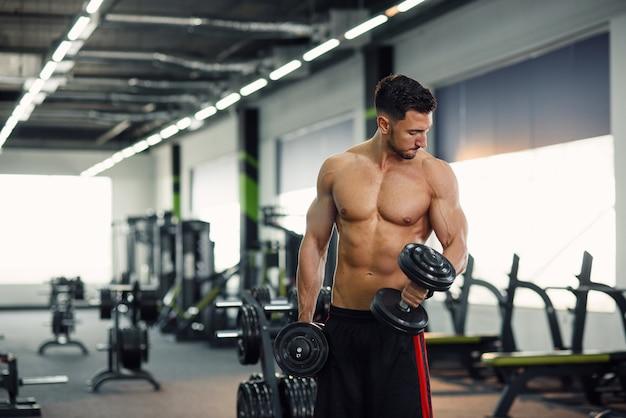 ジムで上腕二頭筋のトレーニング中にダンベルでワークアウト魅力的なフィットネス男。スポーティで健康的なコンセプト。