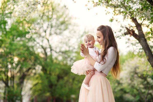 母は咲く木の中で彼女の腕の中で彼女の小さな娘を保持します。ママと彼女の小さな赤ちゃんは、ピンクの家族の外観のドレスを着ていました。