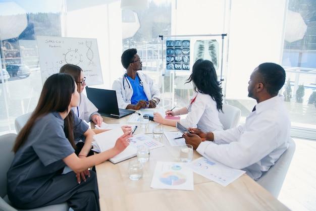 Молодой афроамериканский врач показывает результаты пациента и обсуждает их с командой. международная группа из пяти медицинских работников проводит встречу в конференц-зале больницы.
