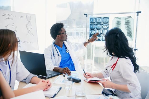 Профессиональная группа многорасовых врачей или стажеров с наставником проводят встречи и делают записи в больничной палате. концепция здравоохранения.