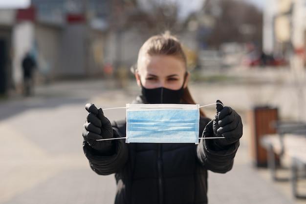 Концепция защиты и эпидемии. молодая взрослая азиатская девушка с покрытым носом и ртом держа в лицевом щитке гермошлема безопасности рук