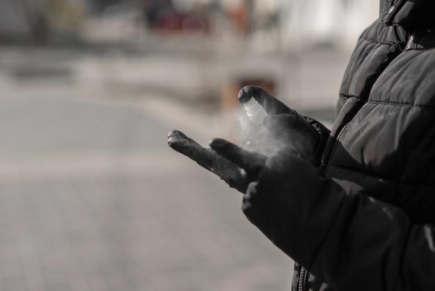 Коронавирусная мировая концепция пандемии. женские руки распыляют дезинфицирующую жидкость для защиты от вирусной инфекции.