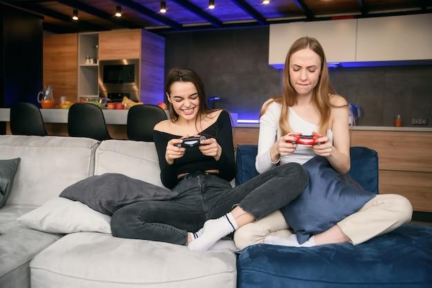 Две подружки страстно играют в компьютерные игры дома, имея карантин. мир пандемии домашней изоляции. наслаждаясь временем, чтобы провести досуг.