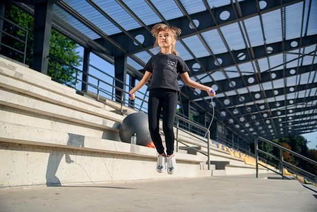 スタジアムで縄跳びでジャンプの女の子。屋外の演習を行うアクティブなフィットネス女性。子供の頃から健康的でスポーティなライフスタイル。
