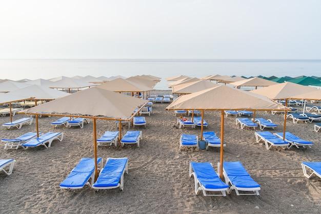日の出の海のビーチで多くのプラスチック製のデッキチェアとパラソル。夏休みのコンセプトです。