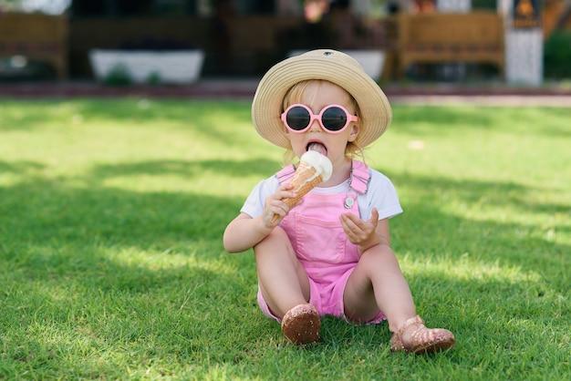 帽子とピンクのサングラスを身に着けたスタイリッシュな幼児の女の子は、暑い晴れた日に緑の芝生で喜びのアイスクリームを食べます。