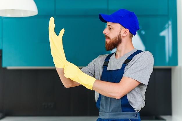 家庭用料理を掃除するために保護ゴム手袋を着用して掃除サービスから手入れの行き届いたひげを持つ魅力的な男