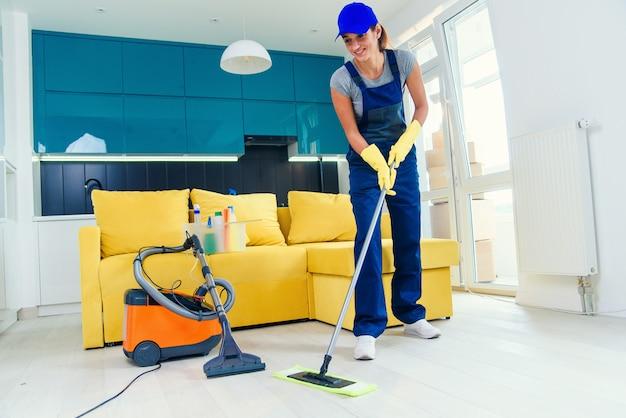 クリーニングのコンセプト。若い女性が台所の床を洗う