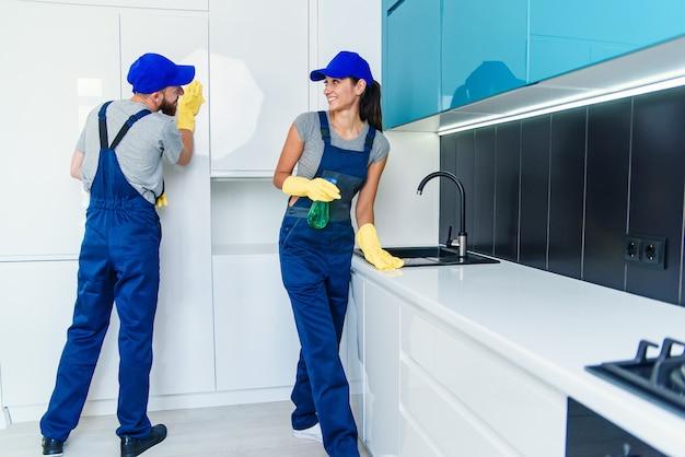 Счастливые профессиональные уборщики молодого человека и милой женщины в голубой форме работы очищая мебель с ветошами и брызг в современной кухне.