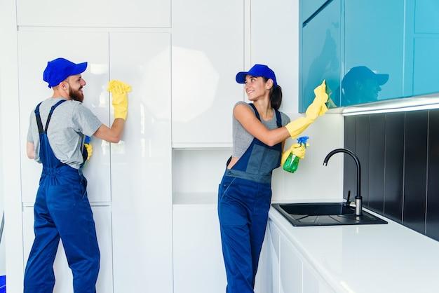 Пара профессиональных уборщиков в синей форме чистит мебель с помощью салфеток и спреев на современной кухне.