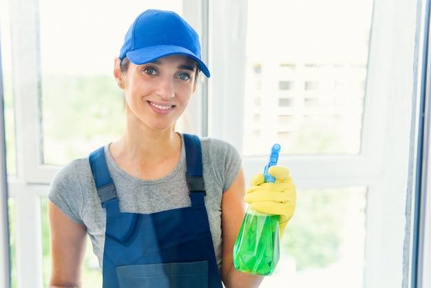 仕事中の専門機器による清掃サービス。カーペットのドライクリーニング、ソファのドライクリーニング、窓や床の洗浄。制服、オーバーオール、ゴム手袋の女性。