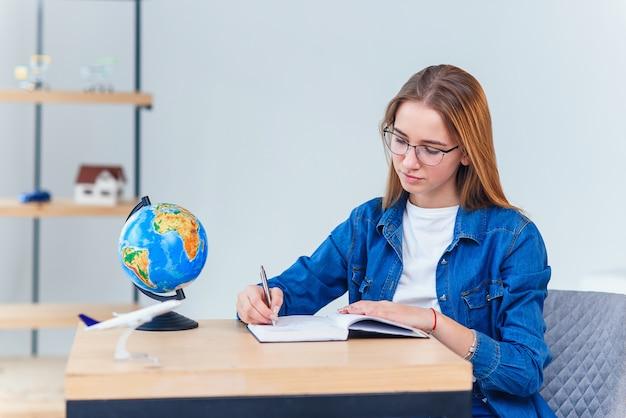 Жизнерадостная предназначенная для подростков девушка на джинсовой одежде изучает дома.