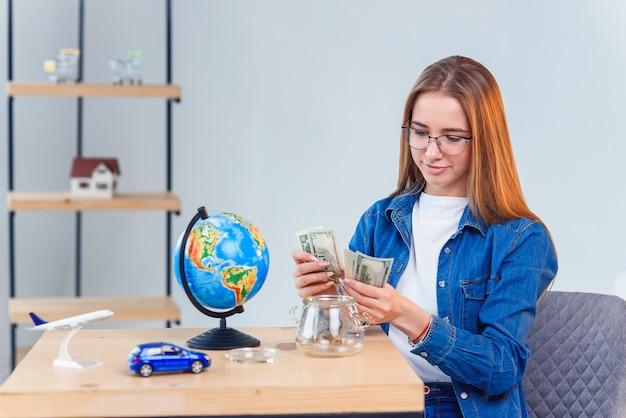 Молодая девушка считает деньги из копилки сидя за столом. понятие финансовой грамотности и сбережений. прозрачная копилка с банкнотами.