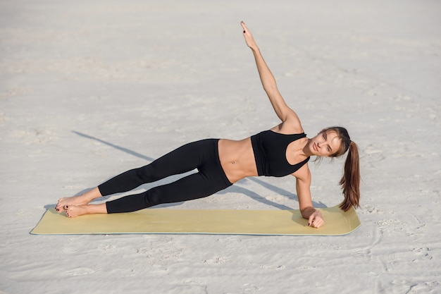 Фитнес женщина красивая сила, тренировка ее ядра тела мышцы с йогой представляют. спортсмен дощат на одной руке, делая боковые дощечки и подтяжку бедер.