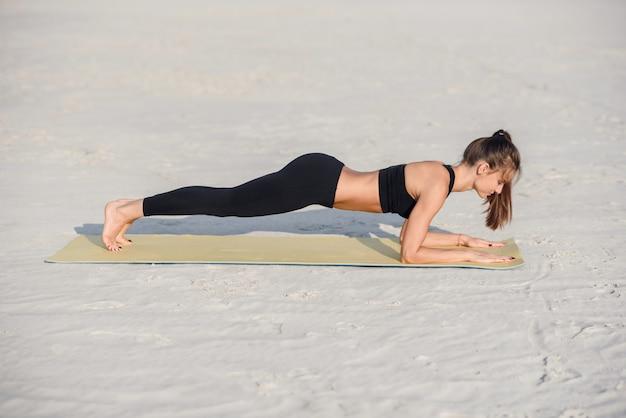 フィットネススポーツヨガと健康的なライフスタイルのコンセプト。ヨガマットで板運動をしている黒のスポーツウェアで美しい女性。