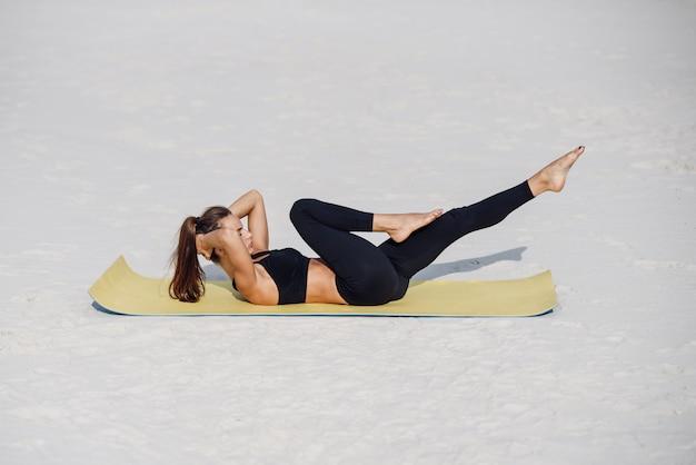 ヨガの練習、プレスアップを行う若い美しい女性は海のビーチで運動をします。フィットネスヨガと健康的なライフスタイルのコンセプト。ヨガマットで運動をしているスポーツウェアで美しい女性。