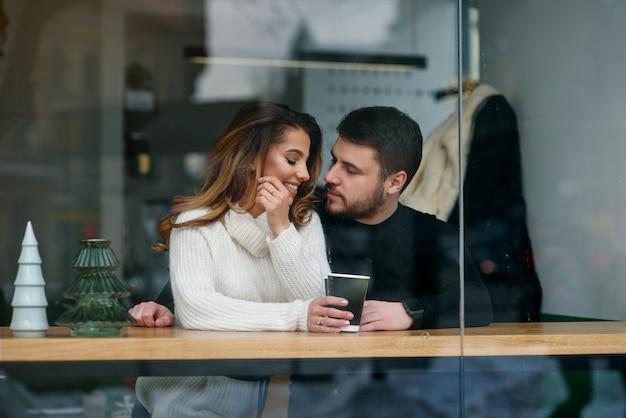 Знакомства в кафе. красивая улыбающаяся девочка со своим парнем, сидя в кафе, наслаждаясь в кофе и разговор.