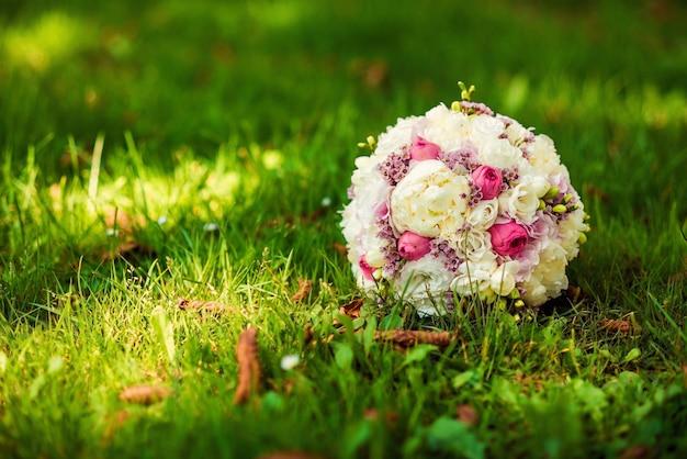 Свадебный букет невесты из нежных розовых и белых цветов, лежащих на зеленой траве. свадебная концепция
