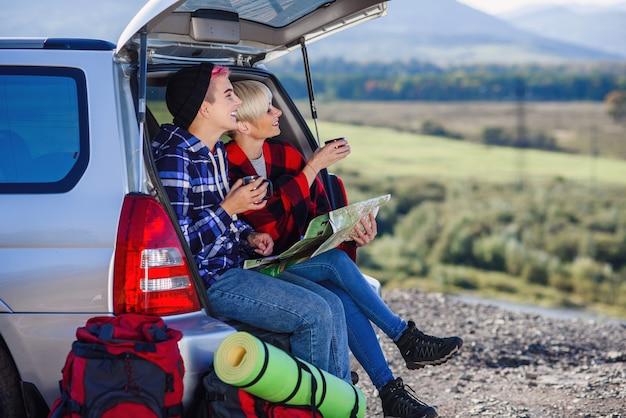 お茶のキャップが付いている車のトランクの上に座って、紙の地図を見て若い友人の旅行者。