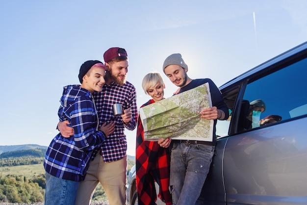 夏の旅行のコンセプトです。自然の中でレンタカー近くの紙の地図を使用して幸せな友達。