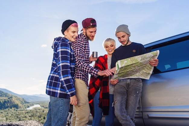 夏の旅行のコンセプトです。自然の中でレンタカー近くの地図を使って幸せな友達。