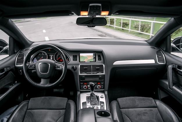 モダンで豪華な高級車のインテリア、ダッシュボード、ステアリングホイール。黒い革のインテリア。
