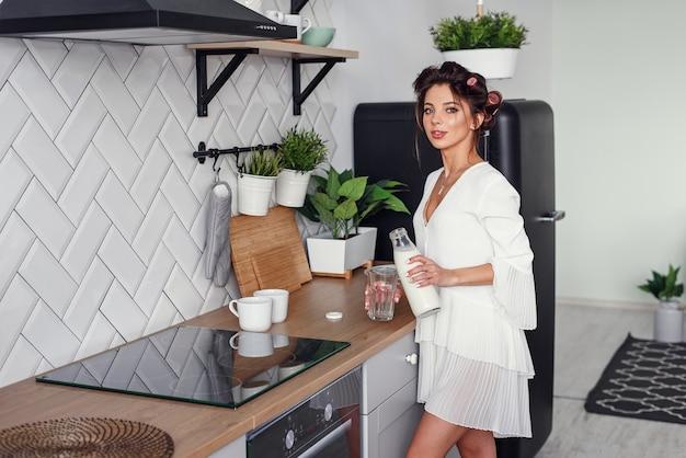 美しい少女は、スタイリッシュな居心地の良いキッチンで、デカンタからグラスに牛乳を注ぎます。健康的な食事とダイエットのコンセプトです。