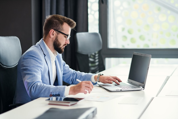 Успешный бородатый бизнесмен в очках и в синем костюме работает с ноутбуком в современном офисе.