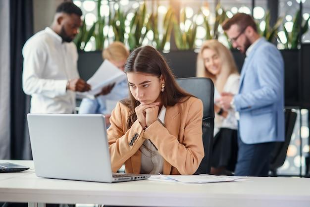 Молодая бизнес-леди работая на таблице офиса перед компьтер-книжкой страдая от чувства головной боли утомленного после трудного рабочего дня.