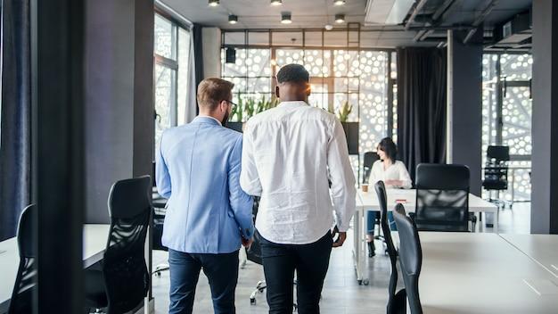 Серьезные кавказские и афро-американские бизнесмены приходят в современный офисный зал и обсуждают детали их сегодняшней работы.