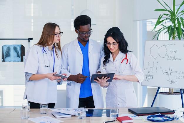 Профессиональная команда многорасовых врачей, имеющих конференцию. многоэтническая группа студентов-медиков. концепция здравоохранения и медицины.
