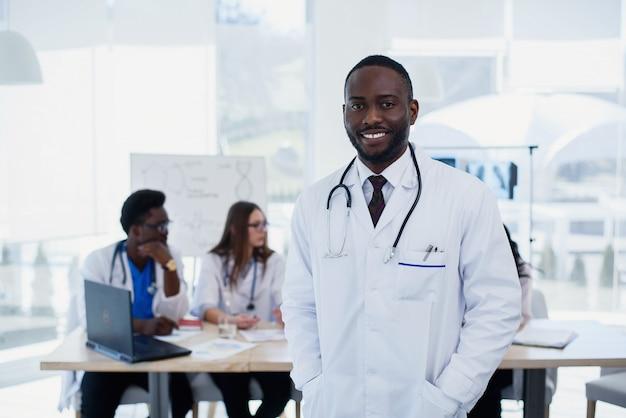 フレンドリーなアフリカの男性医師の肖像画。医療助手または聴診器で白い制服を着た学生。会議室で医療グループとハンサムな男性医師。