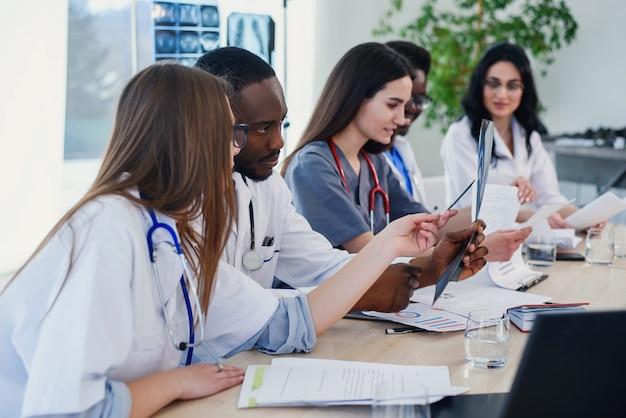 Группа врачей изучает историю болезни пациента. команда многонациональных молодых врачей, имеющих встречу в конференц-зале в современной яркой больнице.