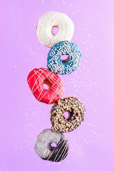 Разноцветные украшенные пончики в движении падения