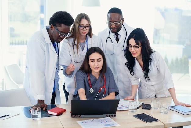 会議室での分析について議論するためのラップトップを使用して多国籍医師のグループ。側面図。